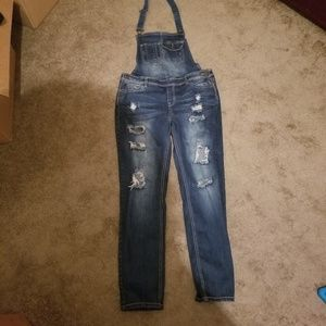 Distressed overall blue jeans
